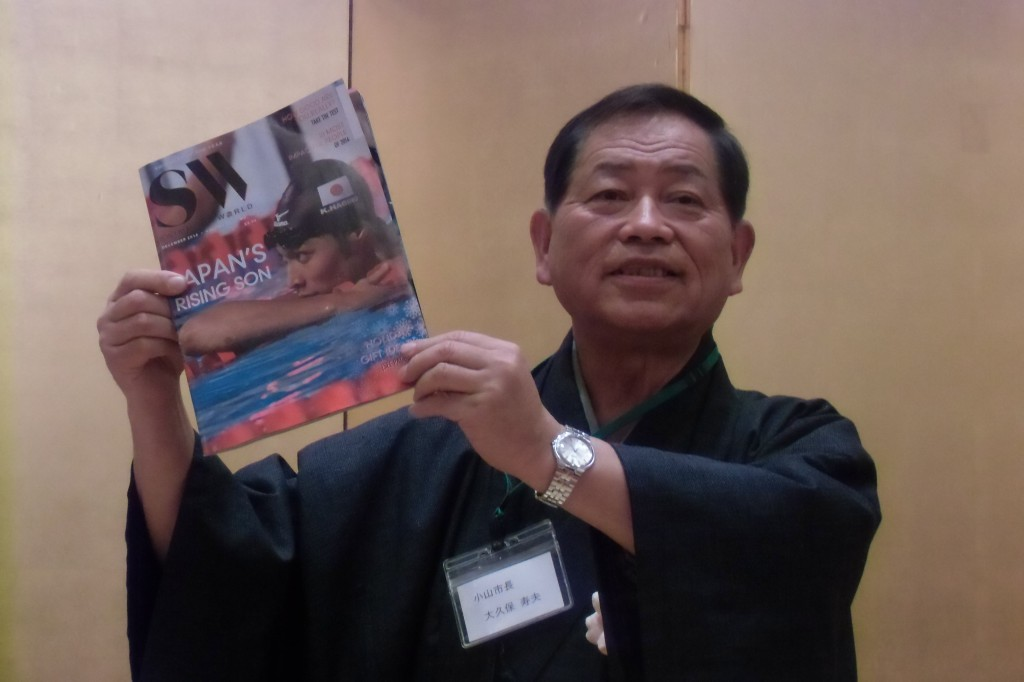 Toshio Okubo poses with Swimming World Magazine with Kosuke Hagino on cover